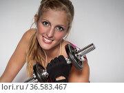 Junge Frau mit sportlichem Outfit betreibt ihr Krafttraining mit ... Стоковое фото, фотограф Zoonar.com/Hans Eder / age Fotostock / Фотобанк Лори