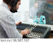 Professional sound engineer regulating level of sound with studio mixer during live radio show. Стоковое фото, фотограф Яков Филимонов / Фотобанк Лори