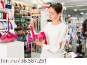 Interested young woman choosing colorful ribbons and braid for dressmaking in sewing supplies shop. Стоковое фото, фотограф Яков Филимонов / Фотобанк Лори