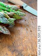 Grüner Spargel und Messer auf altem Holztisch. Стоковое фото, фотограф Zoonar.com/Thomas Klee / easy Fotostock / Фотобанк Лори