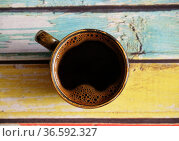 Fresh hot black coffee in ceramic espresso cup. Top view, close-up. Plank color wood background. Стоковое фото, фотограф Кристина Сорокина / Фотобанк Лори