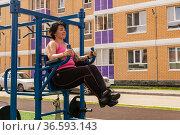 Young woman performs exercises outdoor using street fitness combo machine. Стоковое фото, фотограф Евгений Харитонов / Фотобанк Лори