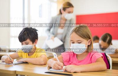 Schoolkids in face masks sitting at desks