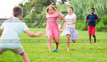 Kids running through grass and playing football