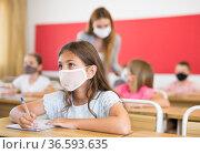 Diligent tween girl in protective mask studying in school. Стоковое фото, фотограф Яков Филимонов / Фотобанк Лори