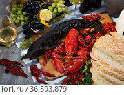 Top view of smoked sturgeon, lobster, crayfishes, bread, cheese, fruits and wine. Стоковое фото, фотограф Яков Филимонов / Фотобанк Лори