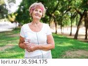 Mature sportswoman in park with bottle of water. Стоковое фото, фотограф Татьяна Яцевич / Фотобанк Лори