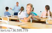 Teenager boy sitting in class room. Стоковое фото, фотограф Яков Филимонов / Фотобанк Лори