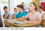 Teen boys and girls sitting at desk in classroom full of pupils during lesson closeup. Стоковое фото, фотограф Яков Филимонов / Фотобанк Лори