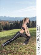 Junge Frau mit sportlichem Outfit betreibt Stretching in freier Natur. Стоковое фото, фотограф Zoonar.com/Hans Eder / age Fotostock / Фотобанк Лори