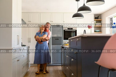 Happy caucasian senior couple dancing together in kitchen and having fun