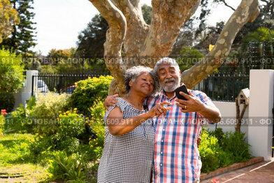 Happy african american senior couple taking selfie in garden