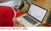 Caucasian woman wearing santa hat making video call at home on laptop with copy space on screen. Стоковое видео, агентство Wavebreak Media / Фотобанк Лори