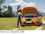 Junge Frau ruft nach einer Autopanne um Hilfe. Стоковое фото, фотограф Zoonar.com/Hans Eder / age Fotostock / Фотобанк Лори