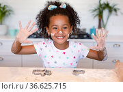 Happy african american girl baking in kitchen, showing hands messy with dough. Стоковое фото, агентство Wavebreak Media / Фотобанк Лори