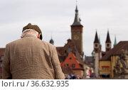 Senior steht auf der Alten Mainbrücke in Würzburg und blickt in Richtung... Стоковое фото, фотограф Zoonar.com/Karl Heinz Spremberg / easy Fotostock / Фотобанк Лори