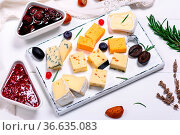 Square pieces of camembert cheese, roquefort, cheddar and brie on... Стоковое фото, фотограф Zoonar.com/Danko Natalya / easy Fotostock / Фотобанк Лори