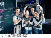 Four happy young men an women posing with laser pistols in their hands in dark laser tag room. Стоковое фото, фотограф Яков Филимонов / Фотобанк Лори