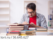 Young male student and too many books in the classroom. Стоковое фото, фотограф Elnur / Фотобанк Лори