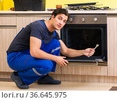 Young service contractor assembling kitchen furniture. Стоковое фото, фотограф Elnur / Фотобанк Лори