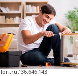 Man assembling shelf at home. Стоковое фото, фотограф Elnur / Фотобанк Лори