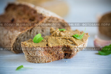 homemade liver pate with bread on a wooden table