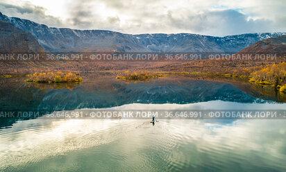 Человек плывет на сапборде по озеру Малый Вудъявр на фоне Хибинских гор. Золотая осень. Вид с высоты