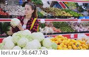 Focused shopper girl picks out a cabbage near the counter, examining it to buy. Стоковое видео, видеограф Яков Филимонов / Фотобанк Лори