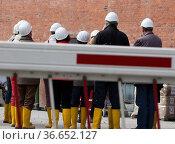 Personen mit Helm und Gummischuhen stehen hinter einer Schranke an... Стоковое фото, фотограф Zoonar.com/Karl Heinz Spremberg / easy Fotostock / Фотобанк Лори