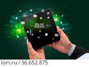 Businessman holding a foldable smartphone with ONLINE FRIENDS inscription... Стоковое фото, фотограф Zoonar.com/rancz / easy Fotostock / Фотобанк Лори