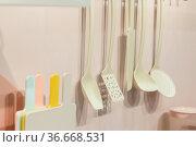 Kitchenware tools household goods plastic hang on the wall, kitchen interior in pastel trending colors. Стоковое фото, фотограф Светлана Евграфова / Фотобанк Лори
