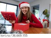 Happy caucasian woman wearing santa hat unpacking present at christmas time. Стоковое фото, агентство Wavebreak Media / Фотобанк Лори