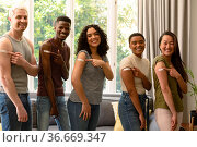 Group of happy diverse female and male friends showing plasters after vaccination. Стоковое фото, агентство Wavebreak Media / Фотобанк Лори