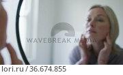 Happy senior caucasian woman in bathroom, looking to mirror, touching face. Стоковое видео, агентство Wavebreak Media / Фотобанк Лори