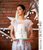 Cheerful bride standing near the brick wall holding wedding cake. Стоковое фото, фотограф Zoonar.com/Dasha Petrenko / easy Fotostock / Фотобанк Лори