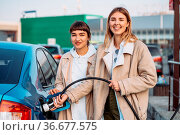 Happy friends refuel car in gas station. Holiday trip of friends. Стоковое фото, фотограф Zoonar.com/Oleksii Hrecheniuk / easy Fotostock / Фотобанк Лори