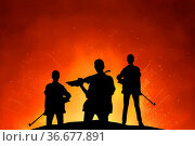 Dark silhouette of female soldiers group with rifle in front of explosion... Стоковое фото, фотограф Zoonar.com/Svetlana Radayeva / easy Fotostock / Фотобанк Лори