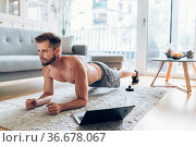 Handsome young man working out at home in the living room. Стоковое фото, фотограф Zoonar.com/Tomas Anderson / easy Fotostock / Фотобанк Лори