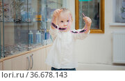 Little girl tries fashion medical glasses near mirror - shopping in... Стоковое фото, фотограф Zoonar.com/Konstantin Shishkin / easy Fotostock / Фотобанк Лори