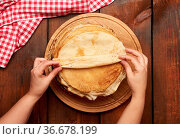 Fried round pancakes on a wooden board and two female hands, brown... Стоковое фото, фотограф Zoonar.com/Danko Natalya / easy Fotostock / Фотобанк Лори