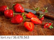 Erdbeeren auf einem Holzbrett mit Messer. Стоковое фото, фотограф Zoonar.com/claudia moeckel / easy Fotostock / Фотобанк Лори
