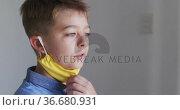 Portrait of a caucasian boy taking off a yellow face mask. Стоковое видео, агентство Wavebreak Media / Фотобанк Лори