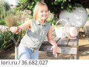 Cheerful little girl with garden tools at table in backyard of the farm. Стоковое фото, фотограф Яков Филимонов / Фотобанк Лори