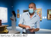 Adult man in face mask standing in gallery. Стоковое фото, фотограф Яков Филимонов / Фотобанк Лори