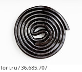 Top view of spiral from black liquorice candy on white plate. Стоковое фото, фотограф Zoonar.com/Valery Voennyy / easy Fotostock / Фотобанк Лори