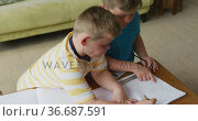 Caucasian boy with his brother sitting at table and learning at home. Стоковое видео, агентство Wavebreak Media / Фотобанк Лори