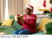 Happy african american senior woman in santa hat opening present at christmas time. Стоковое фото, агентство Wavebreak Media / Фотобанк Лори