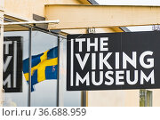 Stockholm, Sweden A sign for the Viking musuem and a Swedish flag. Редакционное фото, фотограф A. Farnsworth / age Fotostock / Фотобанк Лори