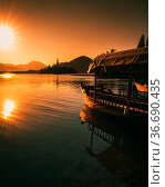 Boats at lake bled slovenia during summer sunset - holiday landscape. Стоковое фото, фотограф Zoonar.com/Maximilian Pawlikowsky / easy Fotostock / Фотобанк Лори