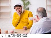 Young man visiting experienced male dentist. Стоковое фото, фотограф Elnur / Фотобанк Лори